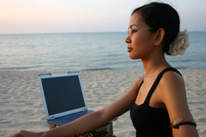 woman w/ laptop on beach